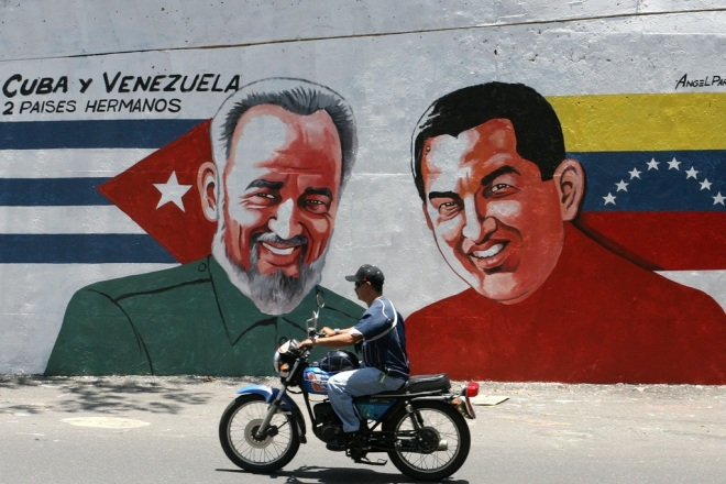 A motorcycle move past a mural depicting Venezuelan President Hugo Chavez (R) and his Cuban counterpart Fidel Castro in Caracas September 2, 2006. Ailing Castro, looking well along the road to recovery, was shown on television on Friday meeting with Chavez after temporarily ceding power a month ago to undergo intestinal surgery REUTERS/Jorge Silva (VENEZUELA)