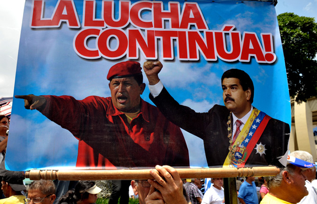 "A man holds a sign reading ""The fight continues"" with the images of former Venezuelan President Hugo Chavez (L) and Venezuelan new President Nicolas Maduro, during a May Day rally in San Jose on May 1, 2013. AFP PHOTO/Ezequiel BECERRAEZEQUIEL BECERRA/AFP/Getty Images"
