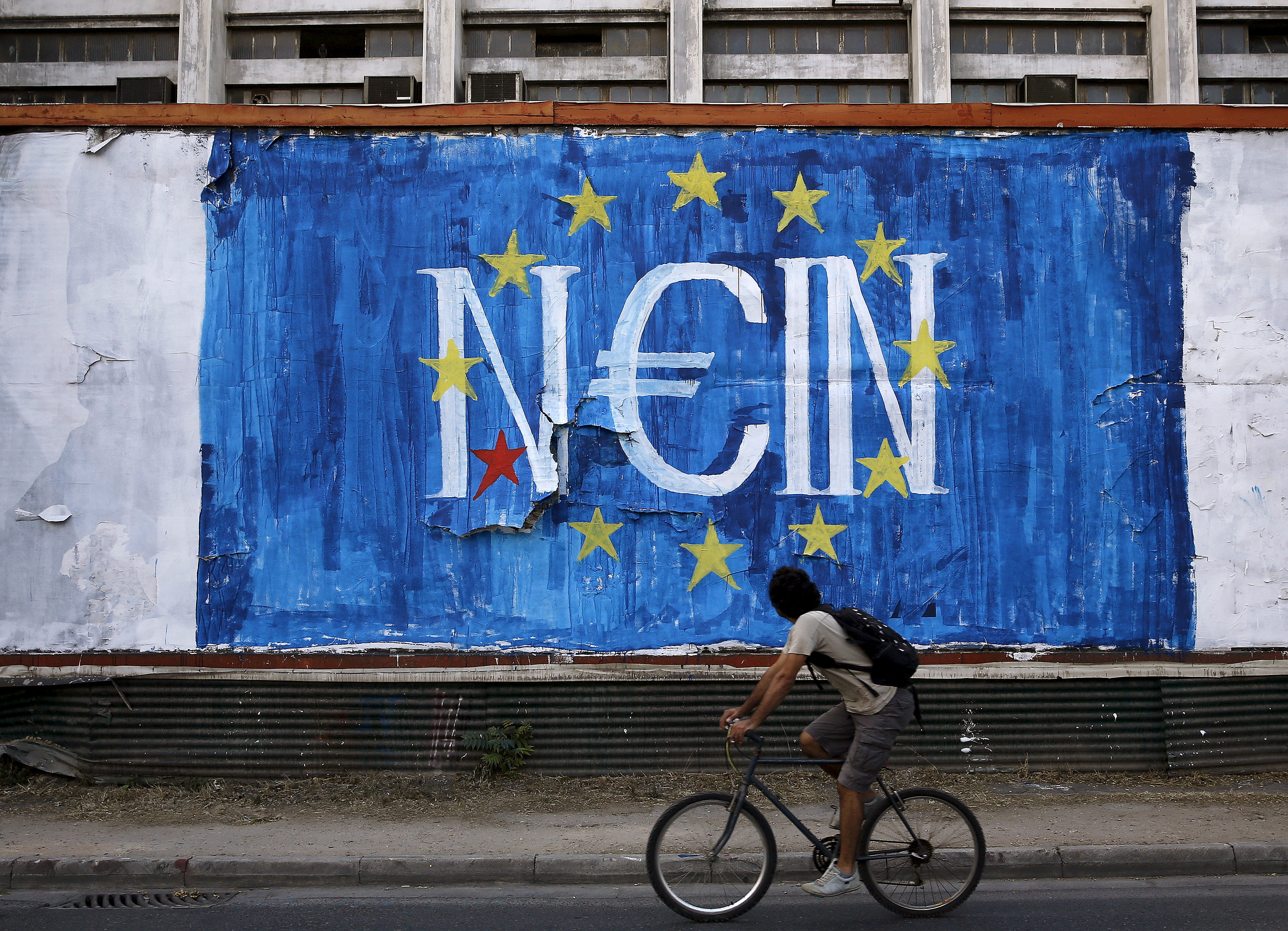 Man cycles by fresh anti-EU graffiti in Athens, Greece